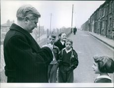 In a back-street Bevan pauses patiently to sign some more autograph books.