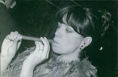 A photo of Marie-Christine Barclay puffing and smoking cigar. 1967