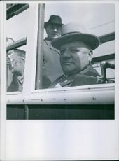 Men siting in the vehicle, looking through window.