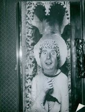 Charles Trenet projecting his face through a painting and making a funny face. Photo taken on December 12, 1963.