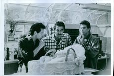 A scene showing Ted Danson, Steve Guttenberg and Tom Selleck looking at the baby in Three Men and a Baby.