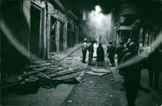 People and uniformed men standing on a street were properties have been damaged in Algeria.