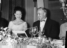 Princess Margaret looking into a book and smiling with a man over a dinner.
