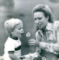 HRH Princess Anne holding a dandelion while her son blows it, 1980.