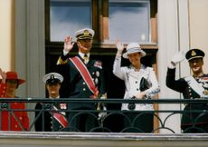 The royal couple waving from the royal palace