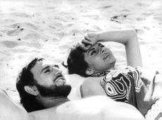 Soraya Esfandiary Bakhtiari with prince Orsini lying on the sand, having sun bath, enjoying each other's company,