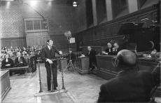Jacques Brel standing in court, on film set.