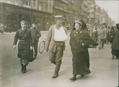 People talking while the nurse walking together with a wounded man after the Post-war.