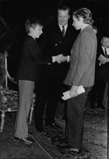Prince Laurent shaking hands with a boy.