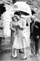 Princess Margaret walking carrying an umbrella.