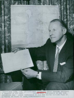 Thor Heyerdahl shows a drawing of his ship at a press conference in New York