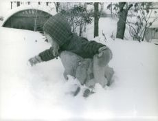 Child playing on snowy field.