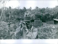 A man, with an animal on his hat, taking pictures during an expedition in New Guinea, 1960.