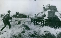 Protected by huge tanks, Russian infantrymen with automatic rifles advance on the front of northeast of Warsaw.