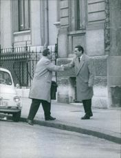 Swedish lawyer Pierre Jaccoud seen shaking hand with another man at the sidewalk of the street