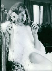 Susan Hampshire holding a flower while sitting, 1966.