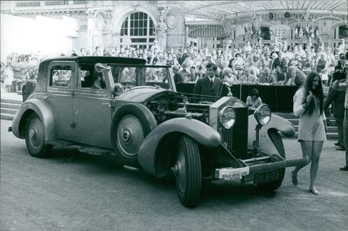 Spectators gathered by the side of the street to have a glimpse of 1930 Rolls Royce Phantom II.