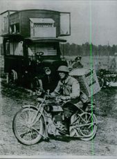 Soldier carrying luggage on his motor cycle and another soldier looking at him.