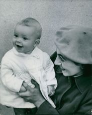 Woman playing with child, smiling.