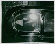 Former British Prime Minister Stanley Baldwin sitting inside the car and looking at outside