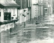 Floods 1966-1989:A Cannoe emerging from a side street.