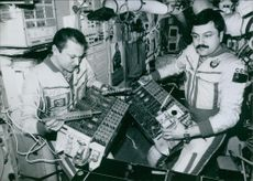 "Soviet Cosmonauts Vladimir Titov and Musa Manarov mending radio communication units abroad the orbital space station ""MIR"", 1989."