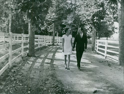 A couple walking holding hands in the middle of the forest.  October 12, 1969