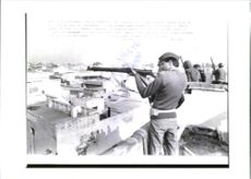 An Indian riot Policeman takes aim.