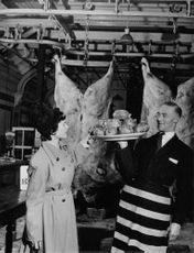 A man showing off a plate of meat to the woman next to him.
