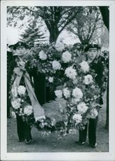 Two soldiers holding a large lei at the funeral.