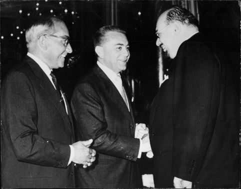 King Farouk shake hands with another man.