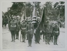 American soldiers march with flags.