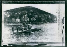 Soldiers riding a boat with a military car.