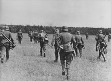 German soldiers fully equipped and walking on a field.