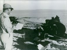 A soldiers standing and reading a paper beside a damaged aircraft parts.