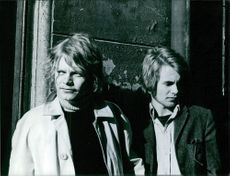 Two men standing together and looking away.