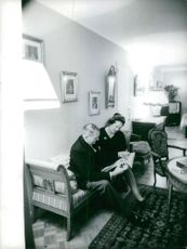 Rene Coty with a woman, reading.