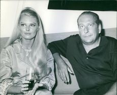 """Claire and Cesare Acquarone sitting on a couch.  """"Claire and Cesare Acquarone"""" 1968"""