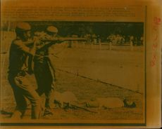 A Indian Policemen fire on a mob.