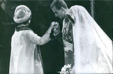 Juan Carlos holding and kissing her mother's hand while Queen Sofia standing beside him during their wedding ceremony.