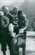 An injured man carried by two people.