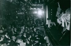 People being entertained by stage performers in a club.