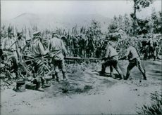 Soldiers holding and taking away the wagon wheel of cannon.
