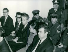 A woman with four men sitting on a bench, in a room, with policemen behind them.