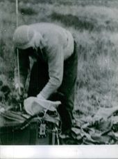 A Russian man inspecting a bag on the field.
