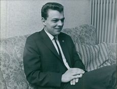 Man sitting on a couch and smiling.