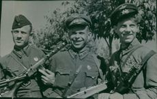 Three smiling soldier in their uniform holds their weapon and smiling during the war, Russia, 1943.