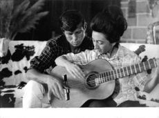 El Cordobes teaching guitar to woman.