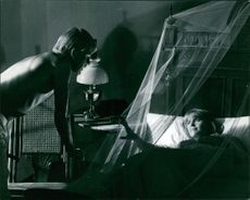 Jane Asher lying in bed with net, Sven-Bertil taube standing beside, on set of The Buttercup Chain.