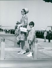 Woman and child during a nation festival, people saluting.